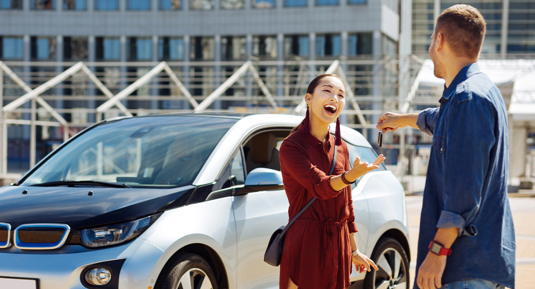 Driver receiving keys to new electric vehicle