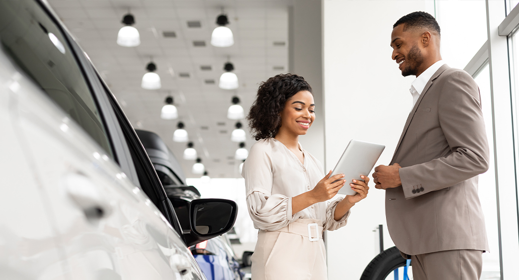 Person car shopping at dealership, speaking with salesperson